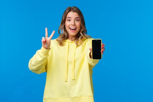 Ottimista carina ragazza europea bionda con taglio di capelli corto, felpa con cappuccio gialla, mostrando gesto di pace kawaii e display del telefono cellulare come usando il filtro fotografico per modificare e pubblicare foto online, blu