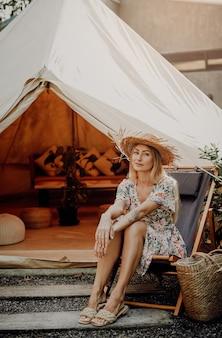Una viaggiatrice ottimista vestita con un bel vestito con un cappello di paglia posa seduta su una sedia sullo sfondo del suo accampamento in thailandia.