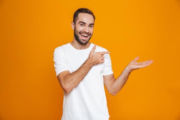 Uomo ottimista con barba e baffi che mostra copyspace sul palmo in piedi, isolato su giallo