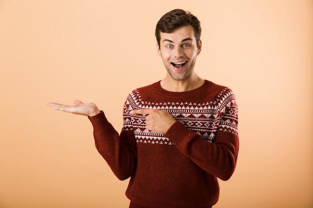 Uomo ottimista con setole che indossa un maglione lavorato a maglia che punta il dito contro copyspace sul palmo, isolato su muro beige