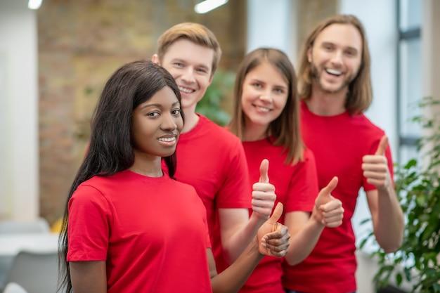 Stato d'animo ottimista. la giovane ragazza americana e gli amici caucasici si offrono volontari in magliette corrispondenti che stanno insieme mostrando il gesto giusto