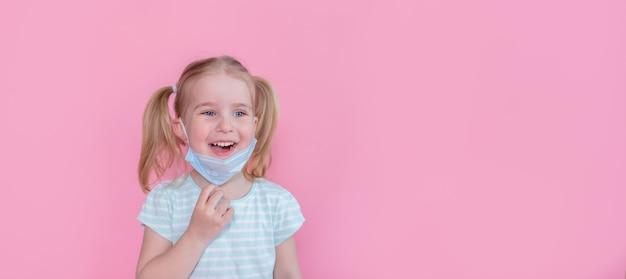 Bambina felice ottimista e sorridente che toglie la maschera medica dal viso su uno spazio rosa che mostra fine della pandemia. copyspace.