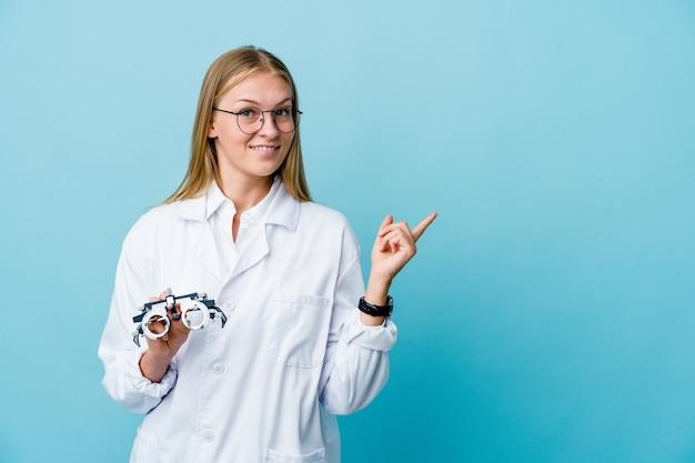 Optometrista donna sorridente e indicando da parte