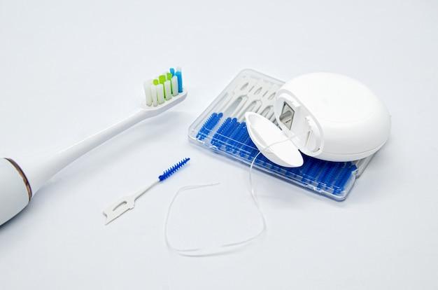 Oral care: spazzolino elettrico, filo interdentale e spazzolini per spazi interdentali su bianco