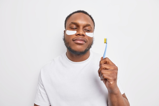 Igiene orale e concetto di cure odontoiatriche. l'uomo di colore serio con la barba applica i cerotti di bellezza