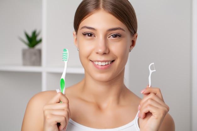 L'igiene orale e l'assistenza sanitaria, le donne sorridenti usano i denti sani bianchi del filo interdentale.