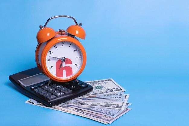 Sveglia e calcolatrice arancione sui dollari delle banconote dei soldi, concetto per la pianificazione aziendale, finanza, risparmio, scadenza di pagamento delle tasse.