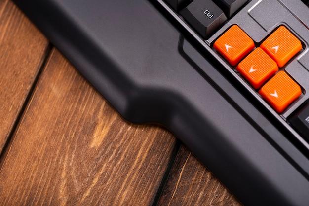 Tasti freccia arancioni su una tastiera nera, pulsanti su, giù, sinistra, destra sulla tastiera di un computer da gioco
