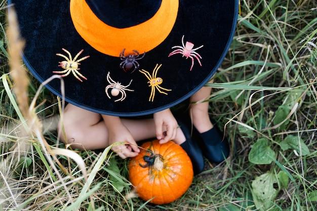Zucca d'autunno arancione nelle mani dei bambini con ragni, decorazioni per le vacanze di halloween.