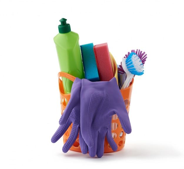 Cestino arancione con spugne da lavaggio, guanti protettivi in gomma, spazzole e detergente in una bottiglia di plastica verde