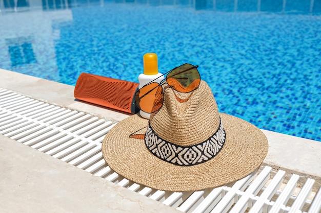 Accessori da spiaggia arancioni crema solare, occhiali da sole, altoparlante musicale e cappello di paglia