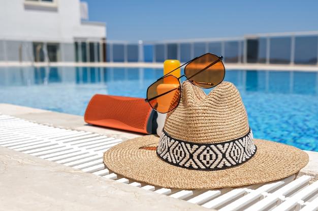 Piscina accessori spiaggia arancione. occhiali da sole, altoparlante musicale e cappello di paglia.