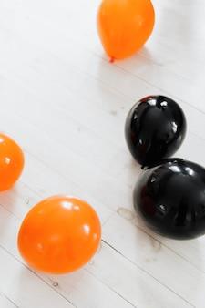Palloncini arancioni e neri sul pavimento di legno bianco