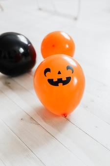 Palloncini di halloween arancioni e neri sul pavimento di legno bianco