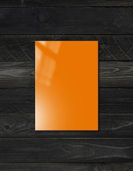 Copertina arancione del libretto isolata su fondo di legno nero, modello di mockup