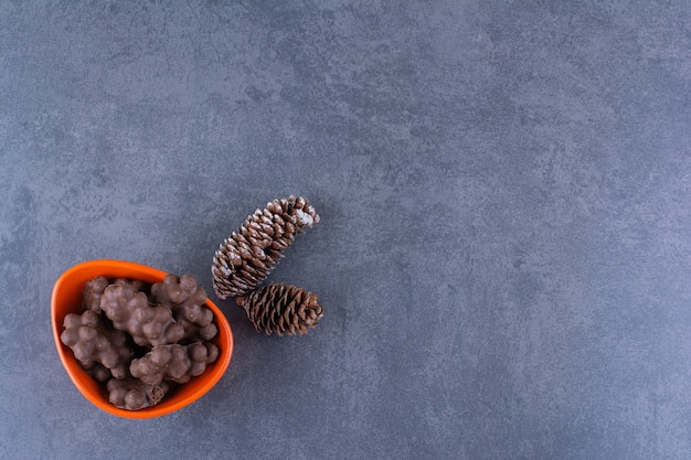 Una ciotola arancione di cioccolato al latte con pigne su una pietra.