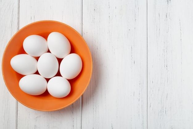Ciotola arancio con le uova bianche sulla tavola di legno con lo spazio della copia