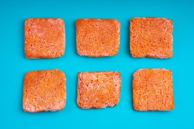 Mattoni arancioni di carote grattugiate congelate. approvvigionamento di alimenti surgelati. semilavorato.
