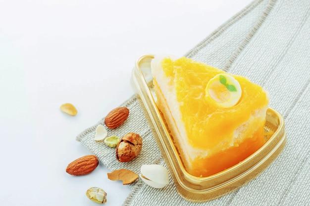 Torta e mandorle arancioni su una priorità bassa bianca.