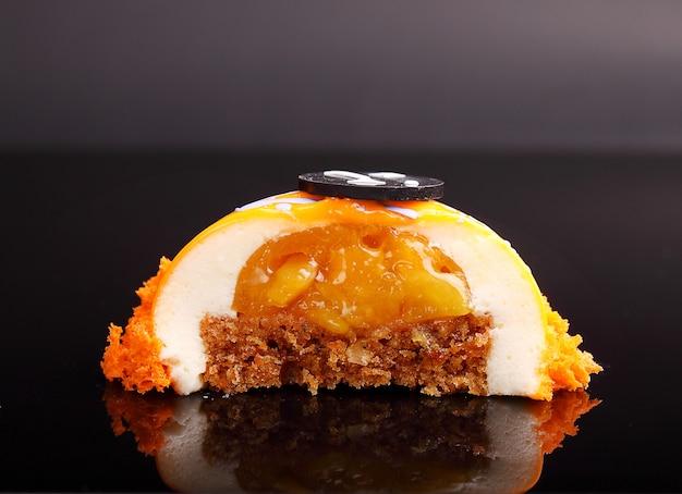 La torta arancione nella glassa dello specchio è decorata con biscotti molecolari su uno sfondo nero