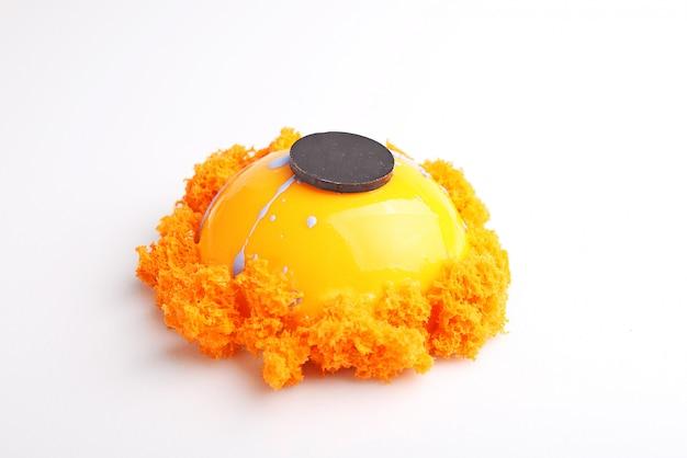 La torta arancione nella glassa dello specchio è decorata con biscotti molecolari. sfondo bianco