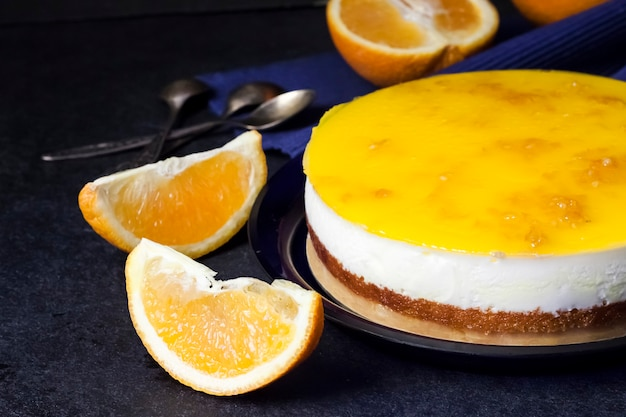 Torta all'arancia con mousse alla crema e gelatina all'arancia su fondo scuro