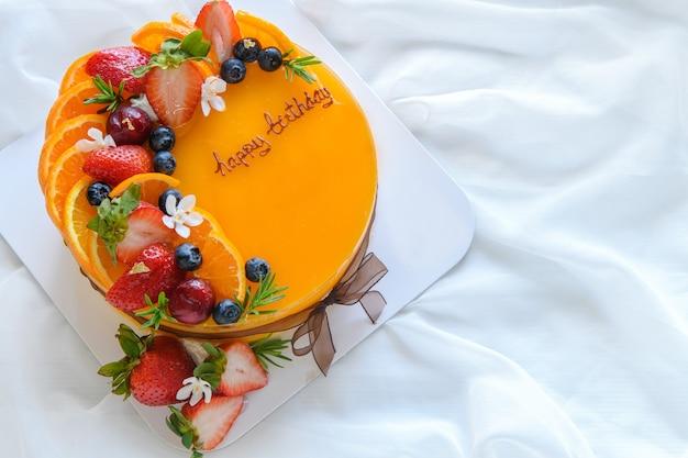 Torta all'arancia con buon compleanno e condita con arancia, fragola, mirtillo sulla superficie del panno bianco, copia spazio e concetto di dessert