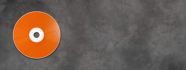 Modello di mockup di etichetta arancione cd dvd isolato su banner orizzontale in calcestruzzo