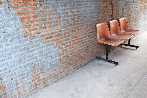 Sedia arancione in piedi in camera su un muro di mattoni arancione