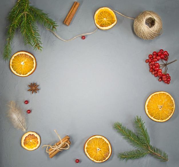 Arancia, cannella, piuma e un rametto di abete rosso, piattamente, copia dello spazio.