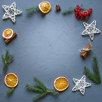Arancia, cannella, stelle e un rametto di abete rosso, piattamente, copia dello spazio.