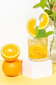 Cocktail all'arancia in un bicchiere su sfondo giallo