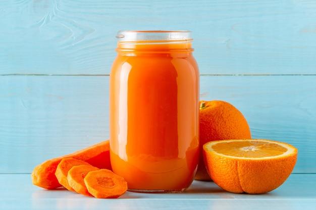 Frullati / succhi di colore arancione in un barattolo su un blu.