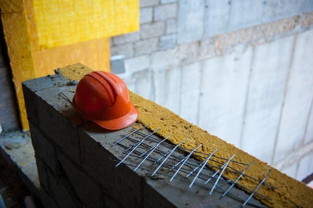 Il casco di un operaio edile arancione poggia sulla muratura del cantiere