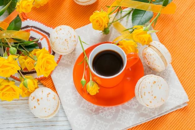 Tazza arancione di caffè nero, fiori di rose gialle e amaretti francesi pastelli dolci sulla tavola di legno bianca. lay piatto