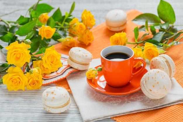 Tazza arancione di caffè nero, fiori di rose gialle e amaretti francesi dolci pastello su tavolo di legno bianco