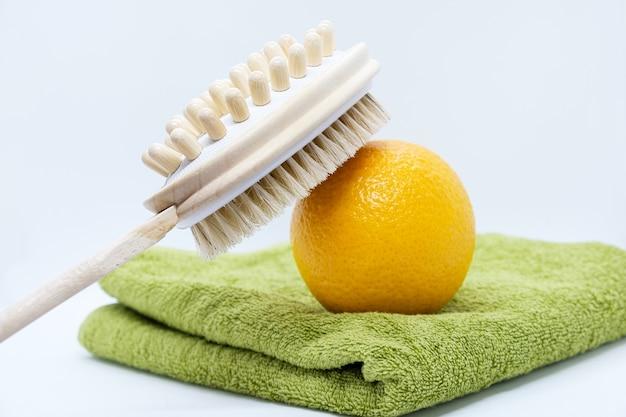 Spazzola per massaggio arancione e a doppia faccia per il corpo e arancione su asciugamano verde su sfondo bianco