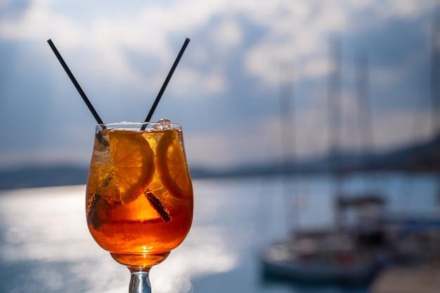 Bevanda all'arancia o cocktail in piedi al tavolino del ristorante o del bar con lo sfondo del mare