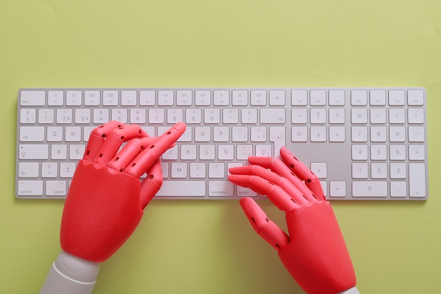 Mani fittizie arancioni su una tastiera con sfondo verde