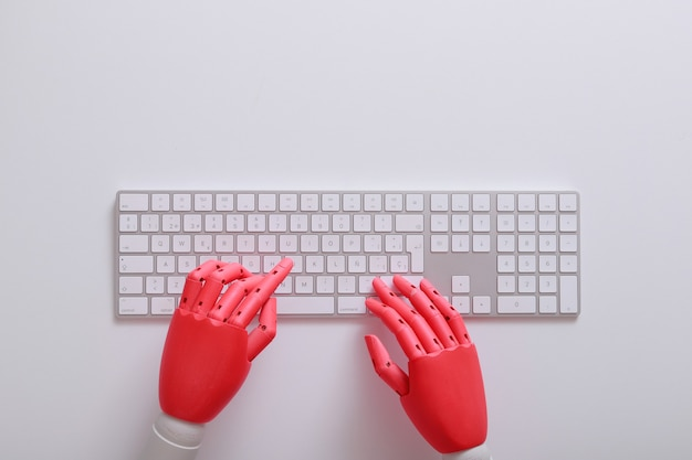 Mani fittizie arancioni su una tastiera con sfondo bianco