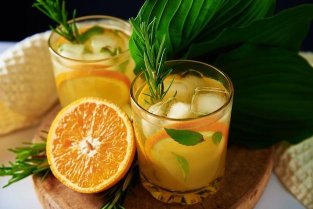 Limonata fresca all'arancia con rosmarino in vetro sul tavolo