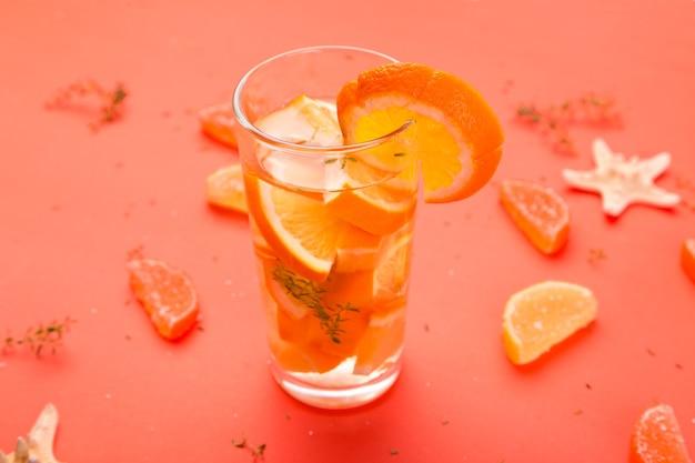 Cocktail di frutta arancione, acqua detox su sfondo arancione