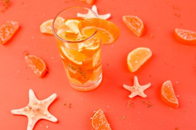 Acqua detox cocktail di frutta arancione sulla superficie arancione fruit