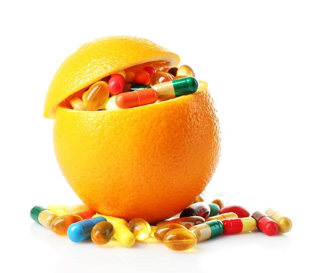 Frutta arancione e pillole colorate, isolate su bianco
