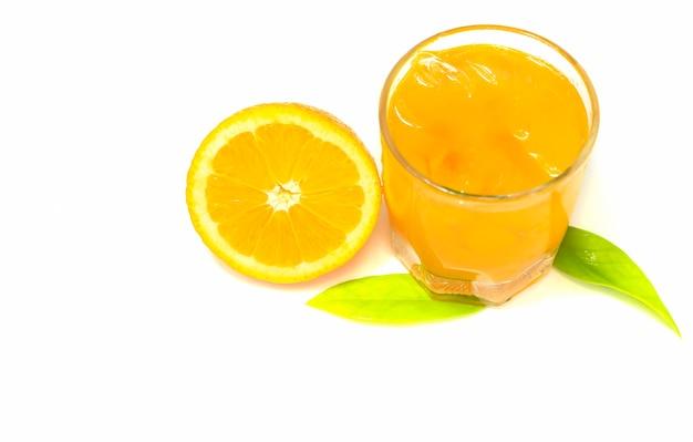 Frutta e vetro arancio su fondo bianco con lo spazio della copia