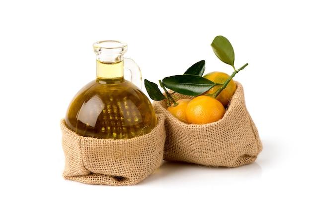 Frutta arancione e olio isolati su sfondo bianco.