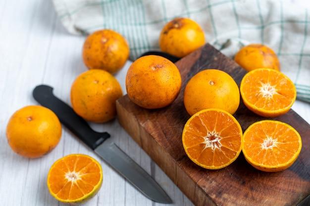 Frutta arancione su legno. mandarini. arance mandarino. arance vang vieng. frutta arancione fresca. frutti sani.
