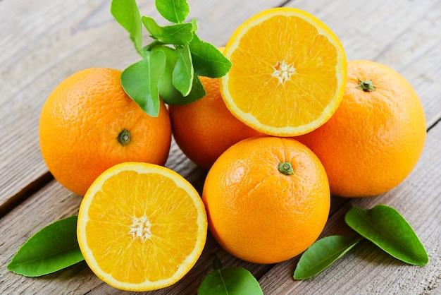 Frutti arancioni con foglia su fondo in legno, fetta d'arancia fresca e foglie frutti sani