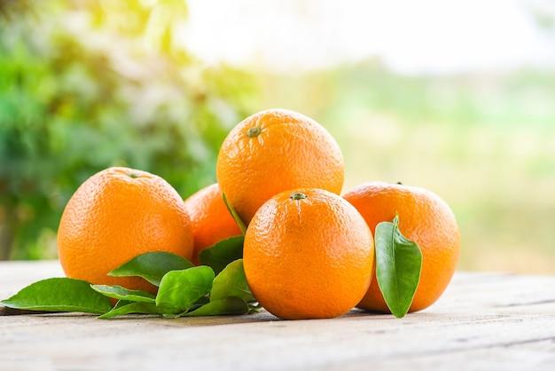 Frutti arancioni con foglia su fondo in legno e natura, arancia fresca con foglie frutti sani