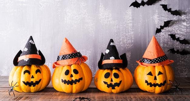 Zucche fantasma arancioni con cappelli da strega e pipistrelli